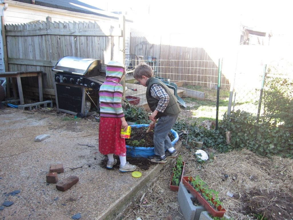 The big children moved the dirt from the old strawberry planter.