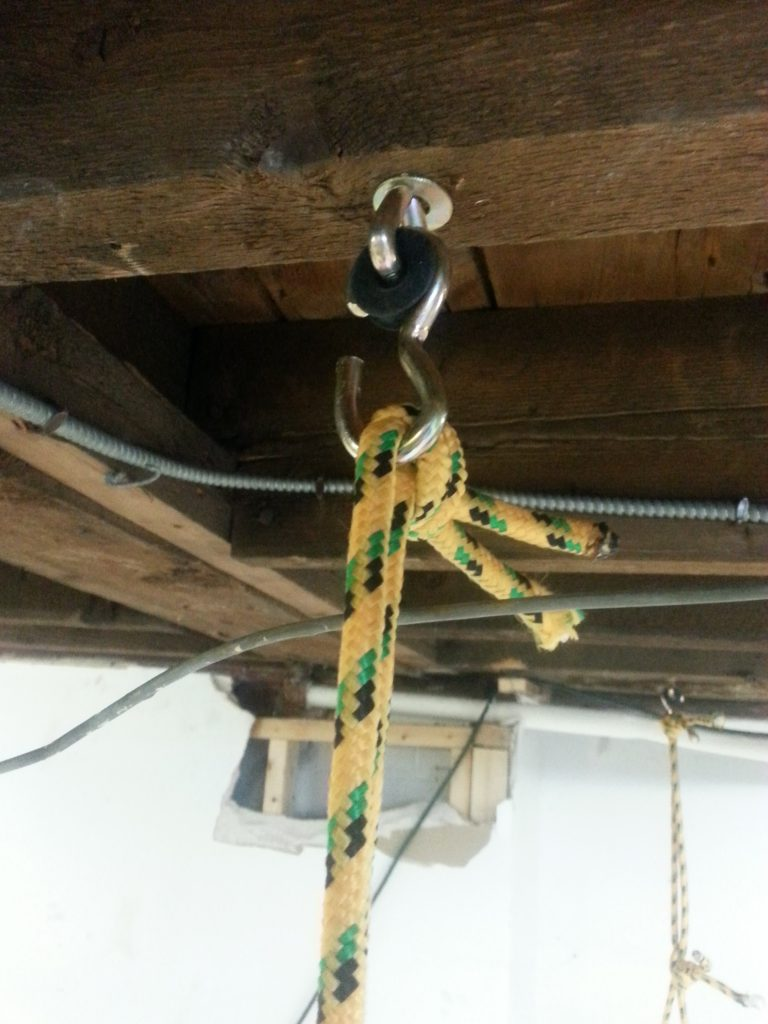The swing gambels screw into the joists. The ladder then hangs from a loop of rope hanging from the gambel.